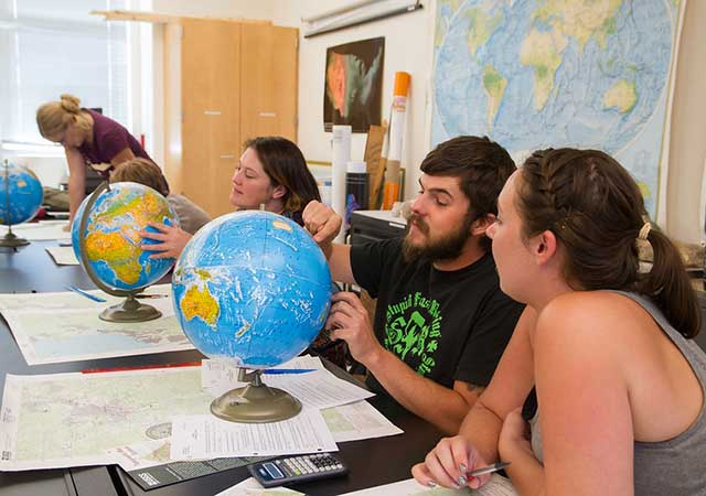 Students studying world globe in geography class