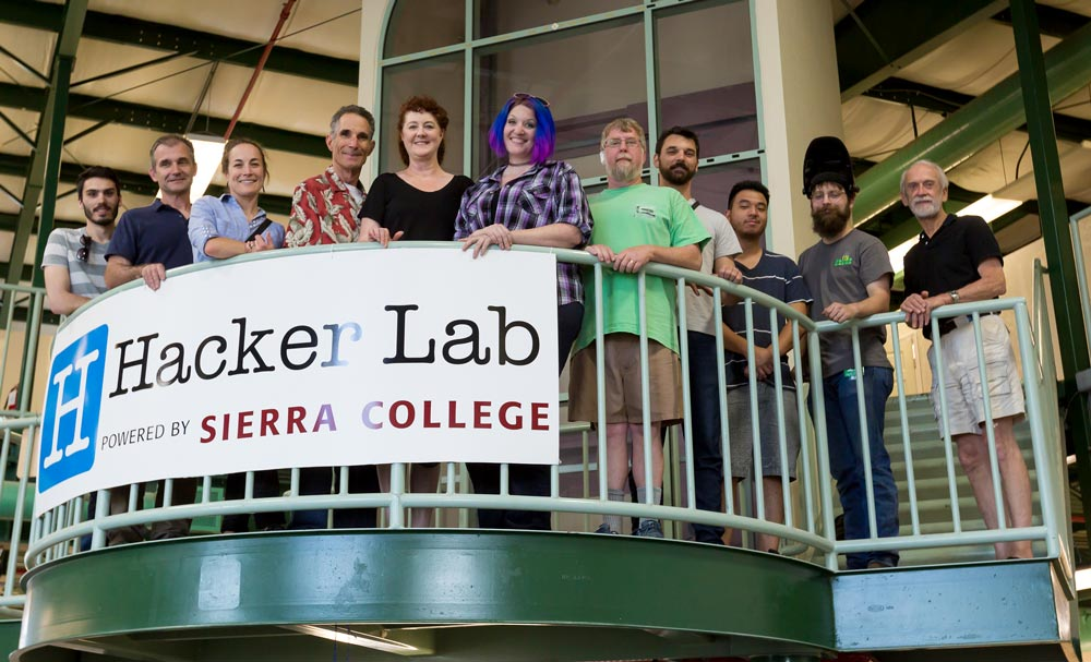 Hacker Lab members pose on a balcony with a Hacker Lab and Sierra College Banner