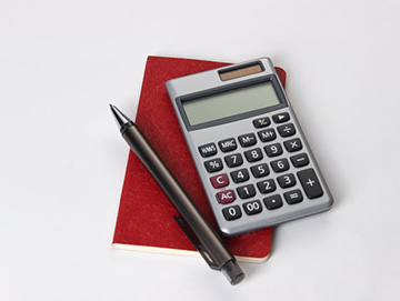 calculator sitting on notepad with pen